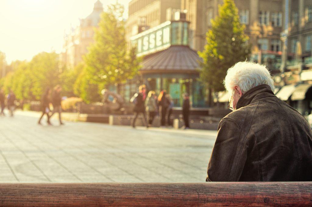 Mann auf brauner Holzbank sitzend