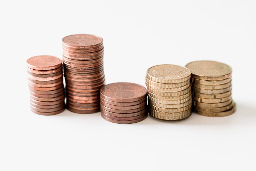 gestapelte runde goldfarbene Münzen auf weißer Oberfläche