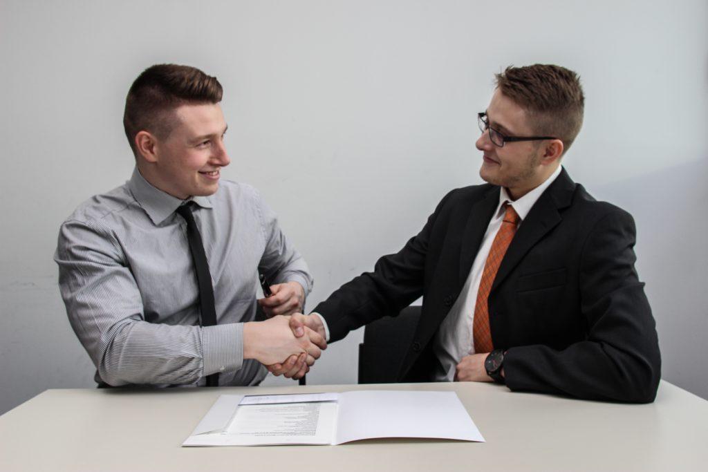 zwei Männer stehen sich gegenüber, während sie sich die Hände schütteln und lächeln.